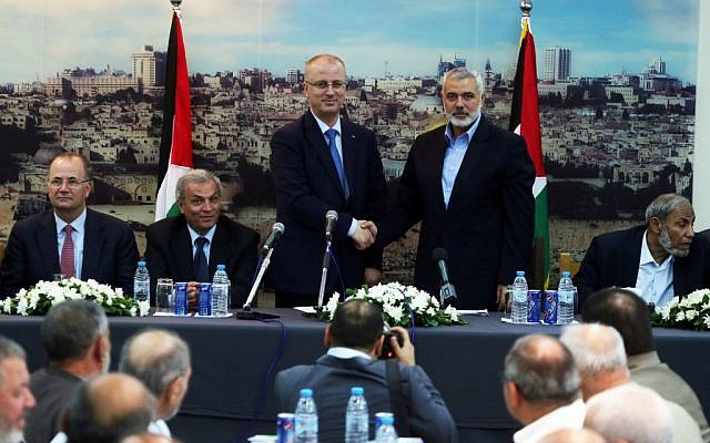 Palestinian Prime Minister Rami Hamdallah shakes hands with senior Hamas leader Ismail Haniyeh, at Haniyeh's house in Gaza city on October 9, 2014