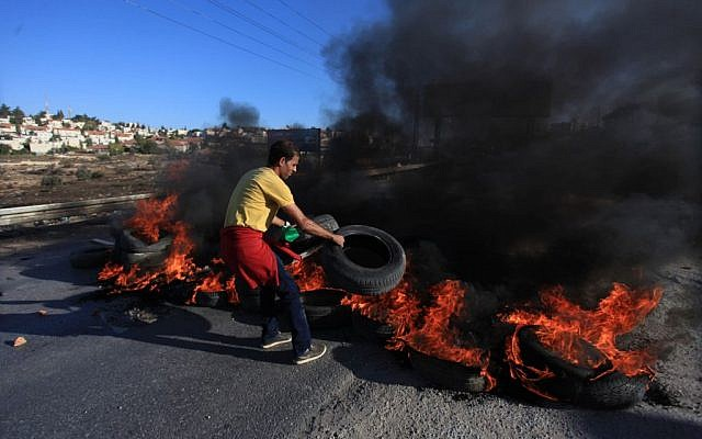 Illustration. A Palestinian youth from the Jilazoun refugee camp places burning tires on the road leading to the settlement of Bet El near Ramallah as he clashes with Israeli soldiers, October 24, 2014 (STR/Flash90)
