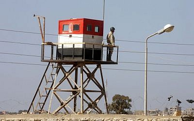 A picture taken from the Palestinian side of the Rafah border crossing in the southern Gaza Strip shows an Egyptian soldier manning a watch tower on the Egyptian side, on October 26, 2014. (photo credit: Abed Rahim Khatib/Flash90)