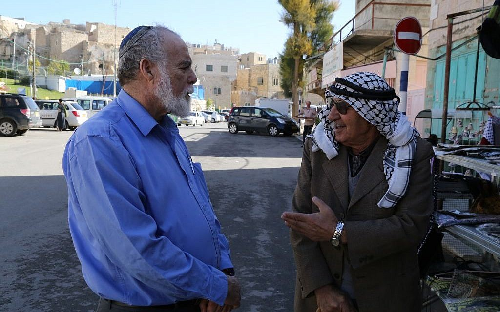A Jewish and an Arab man outside the Tomb of the Patriarchs in Hebron, December 10, 2014 (Gershon Elinson/Flash90)