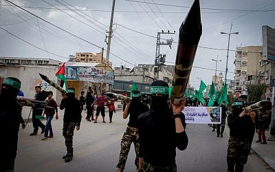 Illustrative: Masked Hamas members carry a model of a rocket during a rally in the central Gaza Strip on December 12, 2014. (Abed Rahim Khatib/Flash90)