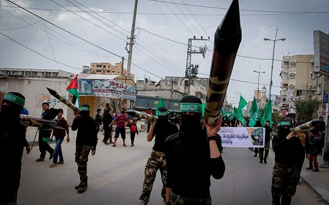 File: Masked Hamas members carry a model of a rocket during a rally in the central Gaza Strip on December 12, 2014. (Abed Rahim Khatib/Flash90)