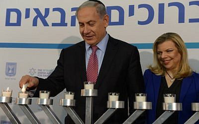 Too much? An article attacks Sara Netanyahu for being mean to house staff. In this photo Benjamin and Sara Netanyahu light candles during the Jewish holiday of Hanukkah in December 2014. (photo credit; Amos Ben Gershon/GPO)