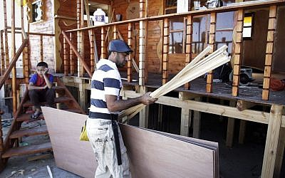 Palestinian carpenter Ibrahim Dokhan, 36, uses wood to rebuild a house damaged during Operation Protective Edge in the southern Gaza Strip city of Rafah, December 31, 2014 (photo credit: Abed Rahim Khatib/Flash90)