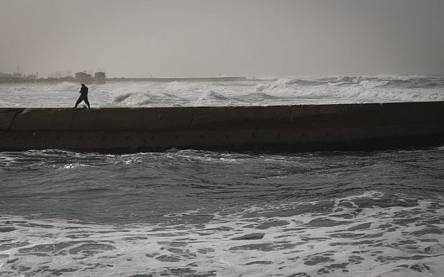 A fisherman walks along the pier in Tel Aviv on a stormy winter day on January 2, 2014. (photo credit: Hadas Parush/Flash90)