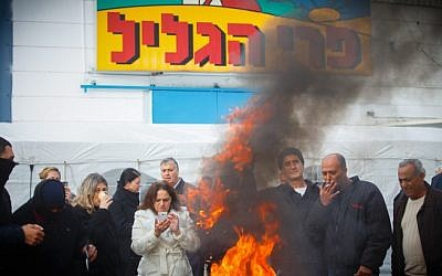 Workers of the Pri HaGalil factory burning tires outside the plant building, January 4, 2015. (photo credit: Flash90)