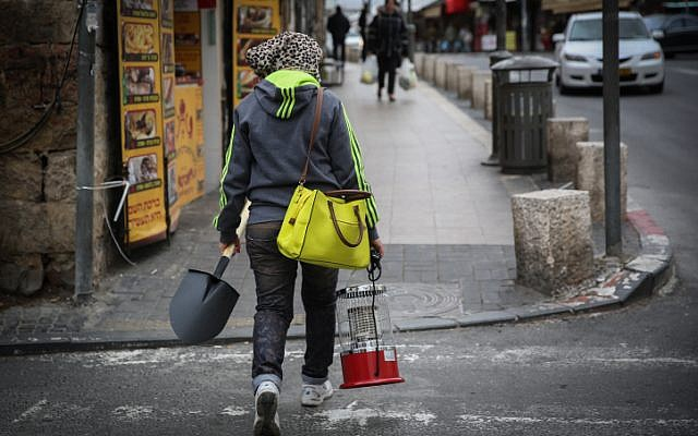 An Israeli woman carries a heater and a shovel, gearing up for the upcoming storm in Jerusalem. January 6, 2014. (photo credit: Hadas Parush/Flash90)