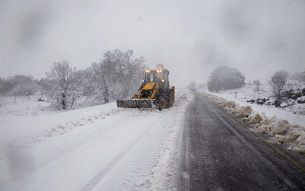 A backhoe plows a snow-covered road in the Golan Heights, northern Israel, Wednesday, January 7, 2015 (photo credit: Basal Awidat/FLASH90)
