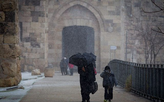 People seen walking by the walls of Jerusalem's Old City Walls as snow begins to fall, Wednesday, January 7, 2015 (photo credit: Miriam Alster/FLASH90)