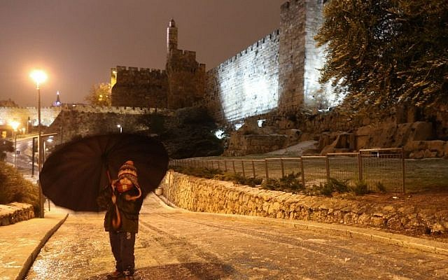 A young girl walks with an umbrella near the walls of the Old City of Jerusalem a winter storm hits Israel, January 07, 2015. (photo credit: Nati Shohat/FLASH90)