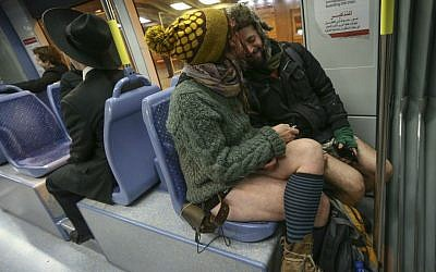 Helena and Bozo snuggle as they ride the Jerusalem light rail train in their underwear for No Pants Train Ride, January 11, 2015. (Nati Shohat/Flash 90)