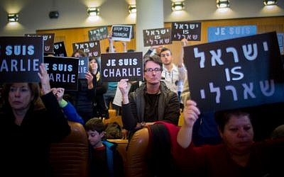 "People hold placards during a remembrance ceremony in Jerusalem City Hall on January 11, 2015, in honor of the 17 victims of the three-day Islamist killing spree in Paris. The Hebrew sign (R) reads ""Israel is Charlie"" (photo credit: Yonatan Sindel/Flash90)"