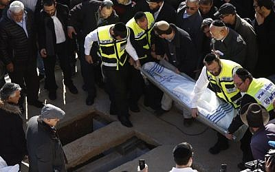 Mourners seen carrying one of the bodies for burial during the funeral ceremony of the four Jewish victims of the Paris kosher grocery attack that was held at Har HaMenuchot cemetery in Jerusalem, on January 13, 2015. (photo credit: Yonatan Sindel/Flash90)