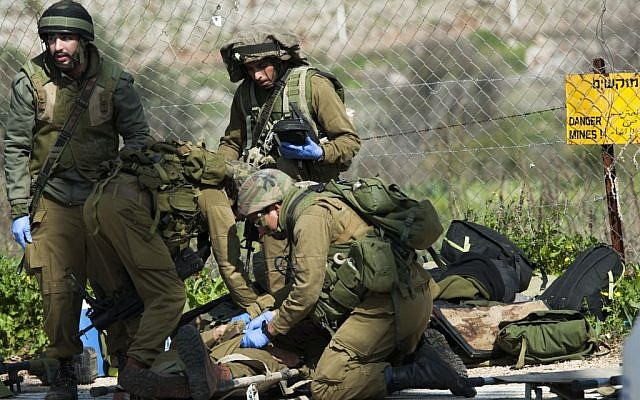 Troops tending to a wounded soldier after a military vehicle came under fire along the Israeli border with Lebanon on January 28, 2015. (Photo credit:  Basal Awidat/Flash90)