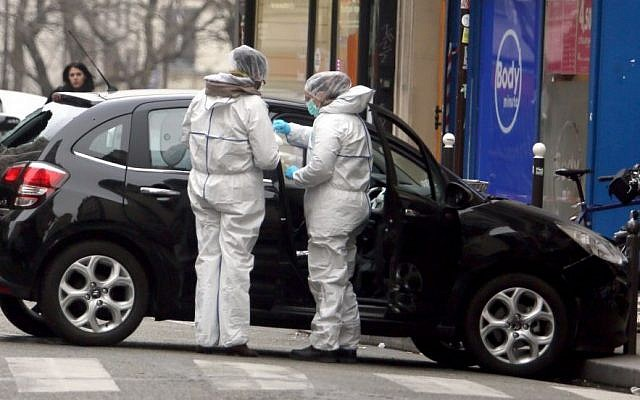 In this Wednesday, Jan. 7, 2015, file photo, forensic experts examine the car believed to have been used as the escape vehicle by gunmen who attacked the French satirical newspaper Charlie Hebdo's office, in Paris.  (Photo credit: AP)