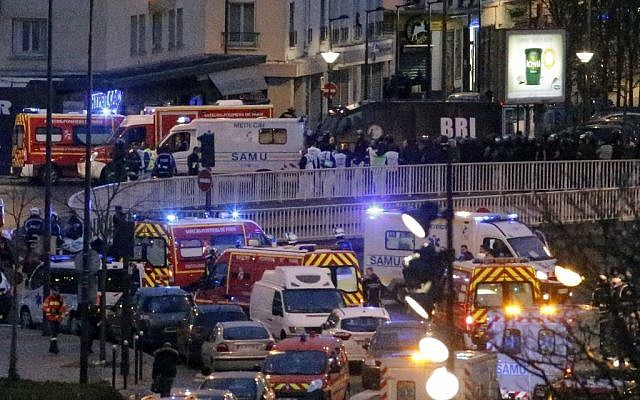 Police officers and rescue workers gather after police stormed a kosher grocery store where a gunman held several hostages, in Paris, Friday Jan. 9, 2015. (photo credit: AP Photo/Francois Mori)
