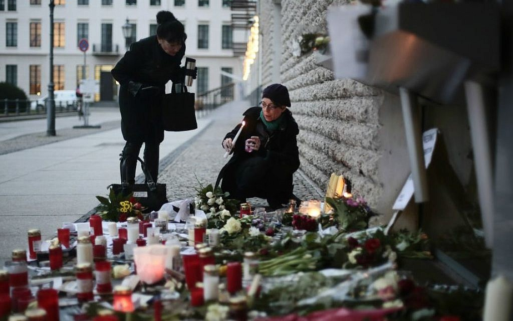 Women light candles to commemorate the victims killed in an attack at the Paris offices of the weekly newspaper Charlie Hebdo, in front of the French Embassy in Berlin, Thursday, Jan. 8, 2015. (photo credit: AP/Markus Schreiber)
