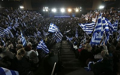 Supporters of Greece's Prime Minister Antonis Samaras wave Greek flags during his final campaign speech at the Taekwondo Indoor Stadium in southern Athens on Friday, Jan. 23, 2015 (photo credit: AP/Petros Giannakouris)