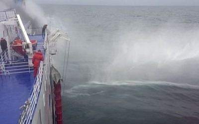 In this image taken from a Dec. 28, 2014 video and made available Wednesday, Dec. 31, 2014 a tug boat passengers sprays water on the Italian-flagged ferry Norman Atlantic after it caught fire in the Adriatic Sea. (Photo credit: AP /APTN)
