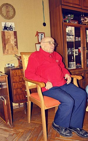 Arkady Bljacher at his home in Brest, Belarus. Bljacher has worked to protect Jewish gravestones in the Belarusian city. In the background are photos he took with the Red Army at the Reichstag. (photo courtesy of The Together Plan)