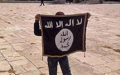 Illustrative photo of a teen holding an Islamic State flag on the Temple Mount in Jerusalem in August 2014. (Facebook)