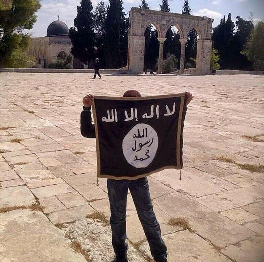 A youngster holding an Islamic State flag on the Temple Mount in Jerusalem in August 2014. (photo credit: Facebook)
