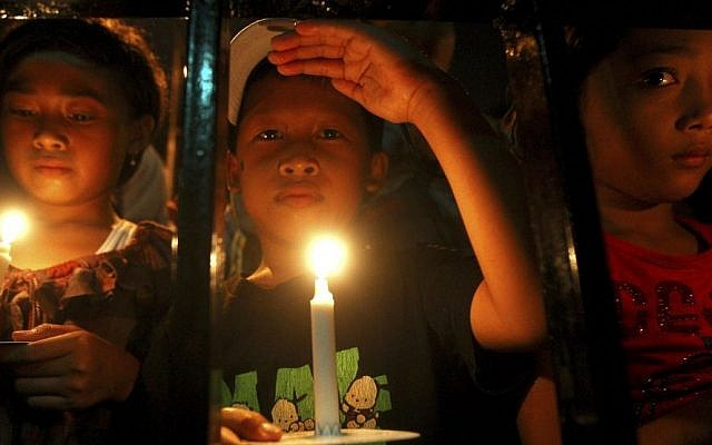 Indonesian children hold candles to pray for the victims of AirAsia Flight 8501 in Surabaya, Indonesia, Wednesday, Dec. 31, 2014. (Photo credit: AP/Firdia Lisnawati)