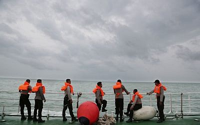 Indonesian police stand on the deck of a National Search And Rescue Agency (BASARNAS) ship during a search operation for the victims of AirAsia flight QZ 8501 on the Java Sea, Indonesia, Saturday, Jan. 3, 2015 (photo credit: AP/Achmad Ibrahim)