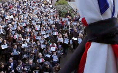 French residents and local Japanese hold 'Je suis Charlie' signs as they attend a special memorial gathering under a French national flag tied with a black ribbon at the French Institute in Tokyo, Japan, Sunday, Jan. 11, 2015 (photo credit: AP/Shizuo Kambayashi)