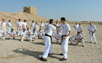Kobi Lichtenstein (center left) leads a Krav Maga training session atop Masada, January 2015. (Courtesy)