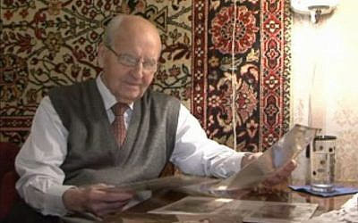 Ivan Martynushkin, who helped liberate Auschwitz, looking at old papers recently. (Screen capture: AFP)