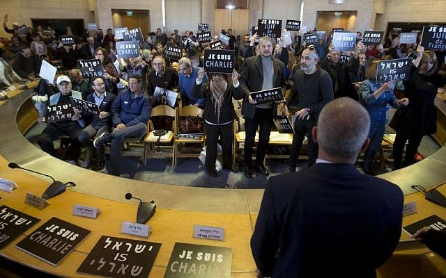 Israelis, including French Jews, hold signs that read 'I am Charlie,' 'Israel is Charlie' and 'I am a Jew of France' during a gathering at the Jerusalem City Hall, Israel, January 11, 2015. (photo credit: AP/Sebastian Scheiner)