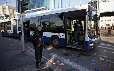 An Israeli police officer secures the scene after a stabbing attack in Tel Aviv on January 21, 2015. (photo credit: AP/Oded Balilty)