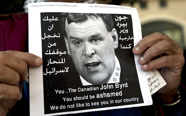 "A Palestinian protester holds a poster with a photo of Canadian Foreign Minister John Baird that reads in Arabic, ""You should be ashamed of your biased position towards Israel,"" during Baird's meeting with Palestinian Authority Foreign Minister Riad Maliki, in the West Bank city of Ramallah, Sunday, Jan. 18, 2015. Dozens of Palestinian protesters have hurled eggs and shoes at the convoy of the visiting Canadian foreign minister. (photo credit: AP Photo/Nasser Nasser)"