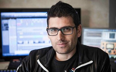 In this photo taken Tuesday, January 6, 2015, Israeli musician Noy Alooshe poses for a photograph in his studio in Tel Aviv, Israel. One of the most unlikely stars of Israel's election campaign is a musical artist whose popular video remixes of stump speeches have rocked YouTube. (photo credit: AP Photo/Dan Balilty)