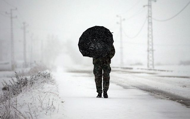 A Lebanese army soldier holds an umbrella as he walks at a main road covered by the snow, in Al-Marj village, in the Bekaa valley, east Lebanon, Wednesday, Jan. 7, 2015. While the storm disrupted life for everyone, it proved particularly trying for the hundreds of thousands of Syrian refugees who live in tents and makeshift shelters in the Bekaa. The storm dumped rain and hail on Lebanon's coast and heavy snows in the mountains and central Bekaa Valley, where gas stations, banks, schools and most shops closed. (Photo credit: AP/Hussein Malla)