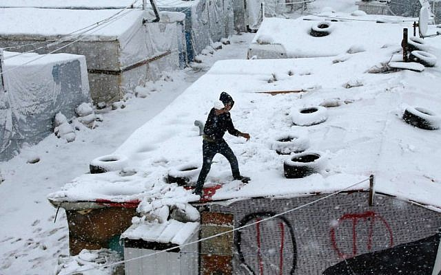 A Syrian boy throws snow from the top of his tent at a refugee camp in Deir Zannoun village, in the Bekaa valley, east Lebanon, Wednesday, Jan. 7, 2015. (Photo credit: AP/Hussein Malla)