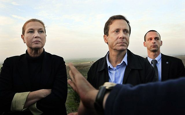 In this Thursday, Dec. 11, 2014 file photo, Israeli politicians Isaac Herzog, right, and Tzipi Livni listen during a tour along the Israel and Gaza Strip border.  (photo credit: AP Photo/Tsafrir Abayov, File )