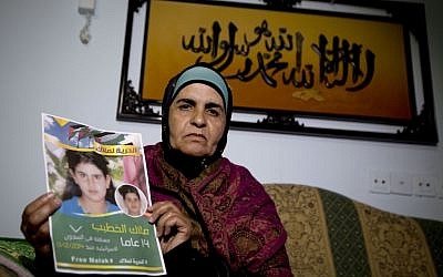 Khawla Al-Khatib, holds a poster of her imprisoned 14-year-old daughter, Malak, in the village of Beitin near Ramallah (Majdi Mohammed/AP Photo)