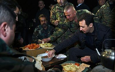 Syrian President Bashar Assad, right, shares a meal with Syrian troops during his visit on the front line in the eastern Damascus district of Jobar, Syria. December 31, 2014 (photo credit: AP Photo/SANA)