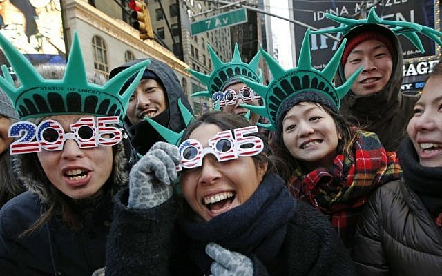 Tourists Teru Udaka, left, and Yuko Yamakata, wearing 2015 glasses, join other friends from Osaka, Japan to celebrate New Year's Eve in Times Square hours before the start of the celebration in New York, Wednesday, Dec. 31, 2014. (Photo credit: AP/Kathy Willens)