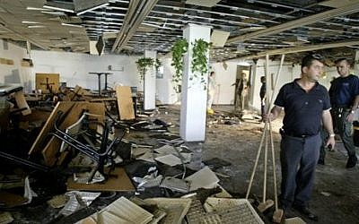 In this July 31, 2002 file photo, workers clean the inside of a cafeteria hours after a bomb exploded at Hebrew University in Jerusalem, killing nine, four of them Americans, and wounding more than 70. (AP Photo/David Guttenfelder)