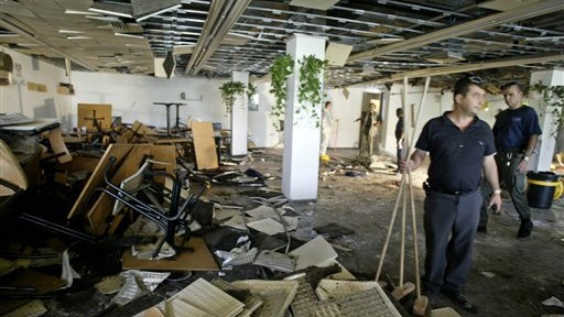 FILE - In this July 31, 2002, file photo, workers clean the inside of a cafeteria hours after a bomb exploded at Hebrew University in Jerusalem, killing nine, four of them Americans, and wounding more than 70. (photo credit: AP Photo/David Guttenfelder, File)