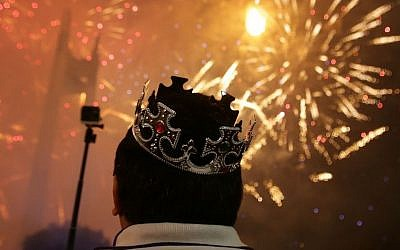 A Filipino watches a fireworks display at the Quezon Memorial Circle in suburban Quezon city, north of Manila, Philippines on Thursday, Jan. 1, 2015. (Photo credit: AP/Aaron Favila)