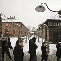 Visitors walk by barbed wire fences at the Auschwitz Nazi death camp in Oswiecim, Poland, Monday, Jan. 26, 2015 (AP Photo/Alik Keplicz)