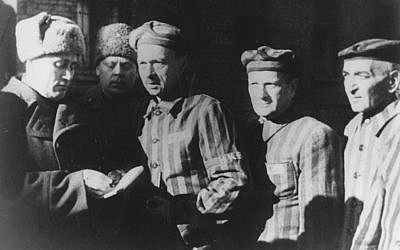 In this file photo dated January 1945, three Auschwitz prisoners, right, talk with Soviet soldiers after the Nazi concentration camp Auschwitz, in Poland, was liberated by the Russians. (Photo credit: AP/FILE)