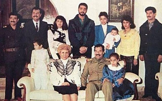Raghad, in the blue blazer, holds her baby in this photograph of the Saddam Hussein family from 1980s. Her new jewelry line was inspired by her father and her husband (Wikimedia Commons)