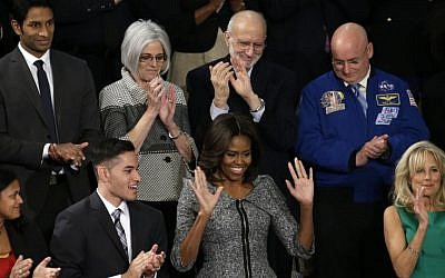 First lady Michelle Obama acknowledges applause on Capitol Hill in Washington, Tuesday, Jan. 20, 2015, before President Barack Obama's State of the Union address before a joint session of Congress. Front row from left are, Astrid Muhammad, Anthony Mendez, Mrs. Obama, and Jill Biden. Second row, from left are, Pranav Shetty, Judy Gross, Alan Gross and Scott Kelly. (Photo credit: AP/Pablo Martinez Monsivais)