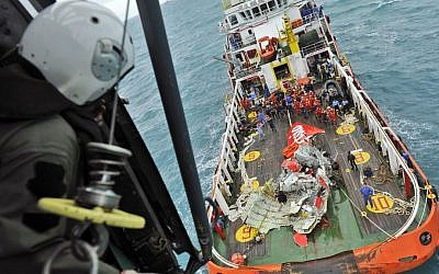 In this photo taken from an Indonesian Air Force helicopter, a portion of the tail of AirAsia Flight 8501 is seen on the deck of a rescue ship after it was recovered from the sea floor of the Java Sea Saturday, Jan 10, 2015. (Photo credit: AP/Prasetyo Utomo, Pool)
