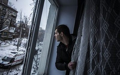 Alexander, 35, looks through a broken window of his flat, hit by Ukrainian Army Artillery, in the Voroshilovsky area, center of Donetsk, Ukraine. Sunday, Jan. 18, 2015. (photo credit: AP Photo/Manu Brabo)